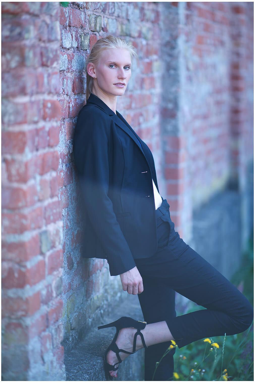 Businessfotografie Businessportrait München Junge Frau Sexy an der Wand angelehnt