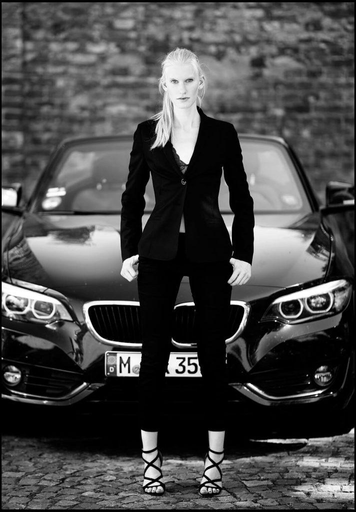 Businessfotografie Businessportrait München Junge Frau Sexy im BMW Vordergund schwarz-weiss