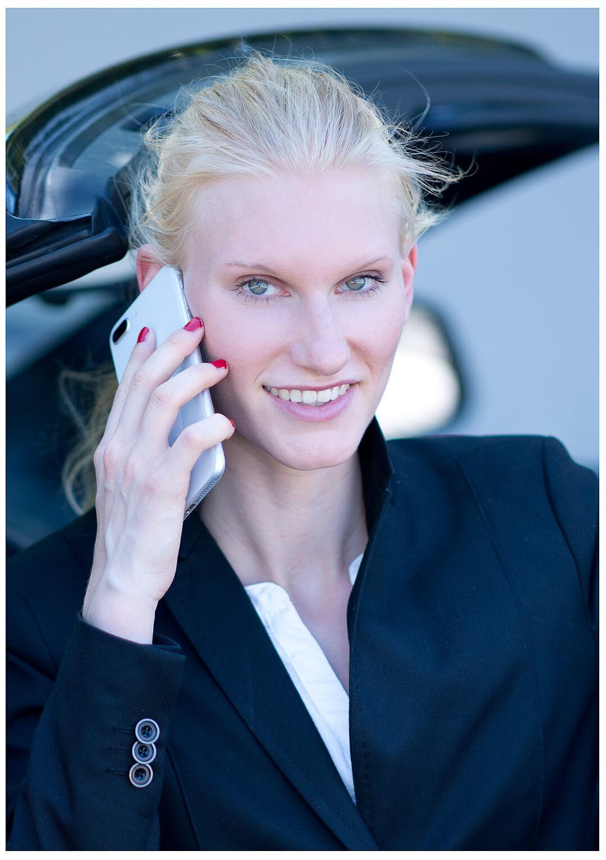 Businessfotografie Businessportrait Junge Frau Sexy sitzend im Auto, telefoniert