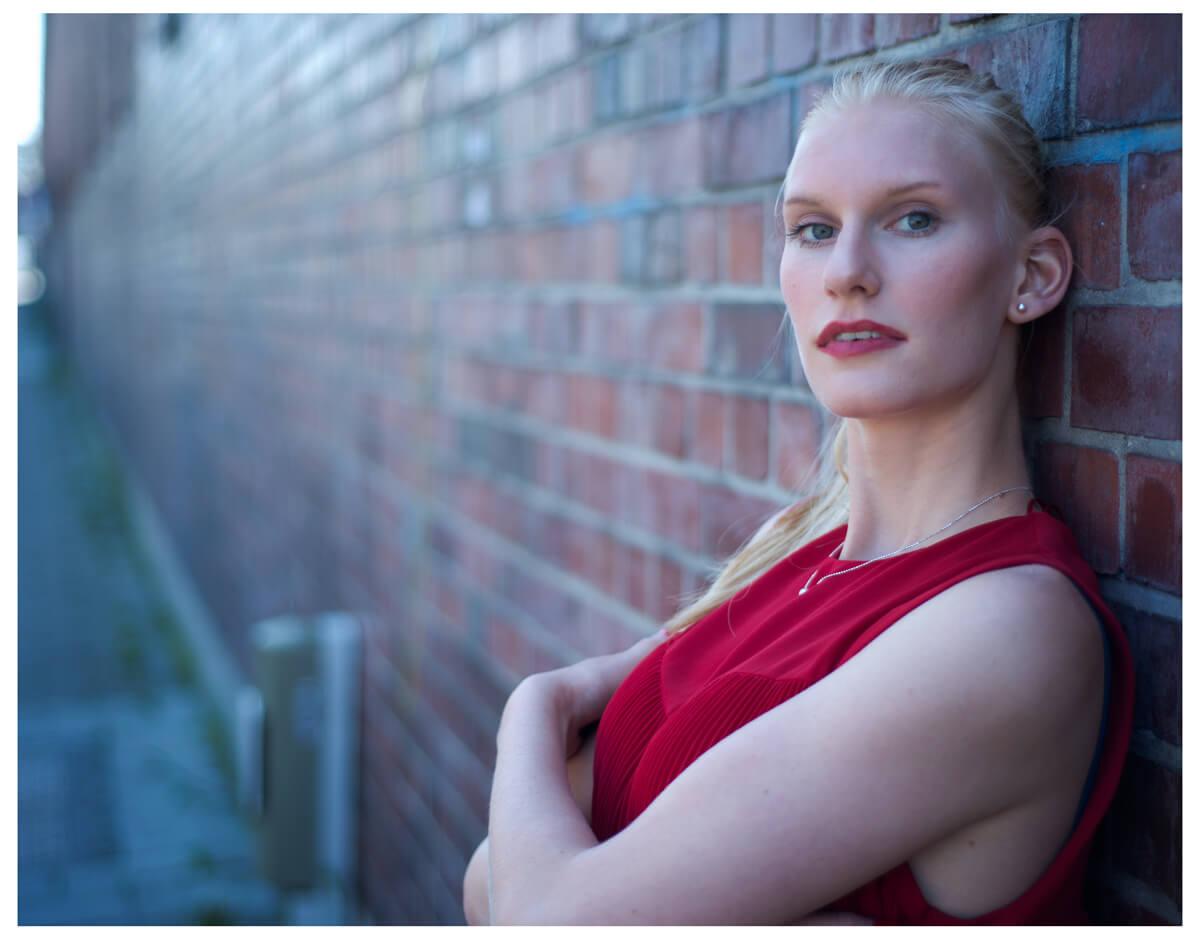Fotograf in München fotografiert ein blondes Model an der alten Wand, im Roten Oberteil, Haende verschraenkt,