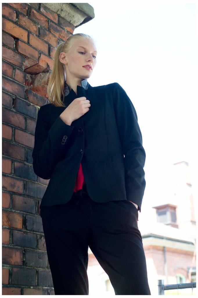 Fotograf in München fotografiert ein blondes Model an der alten Wand, von unten fotografiert, Haende verschraenkt,