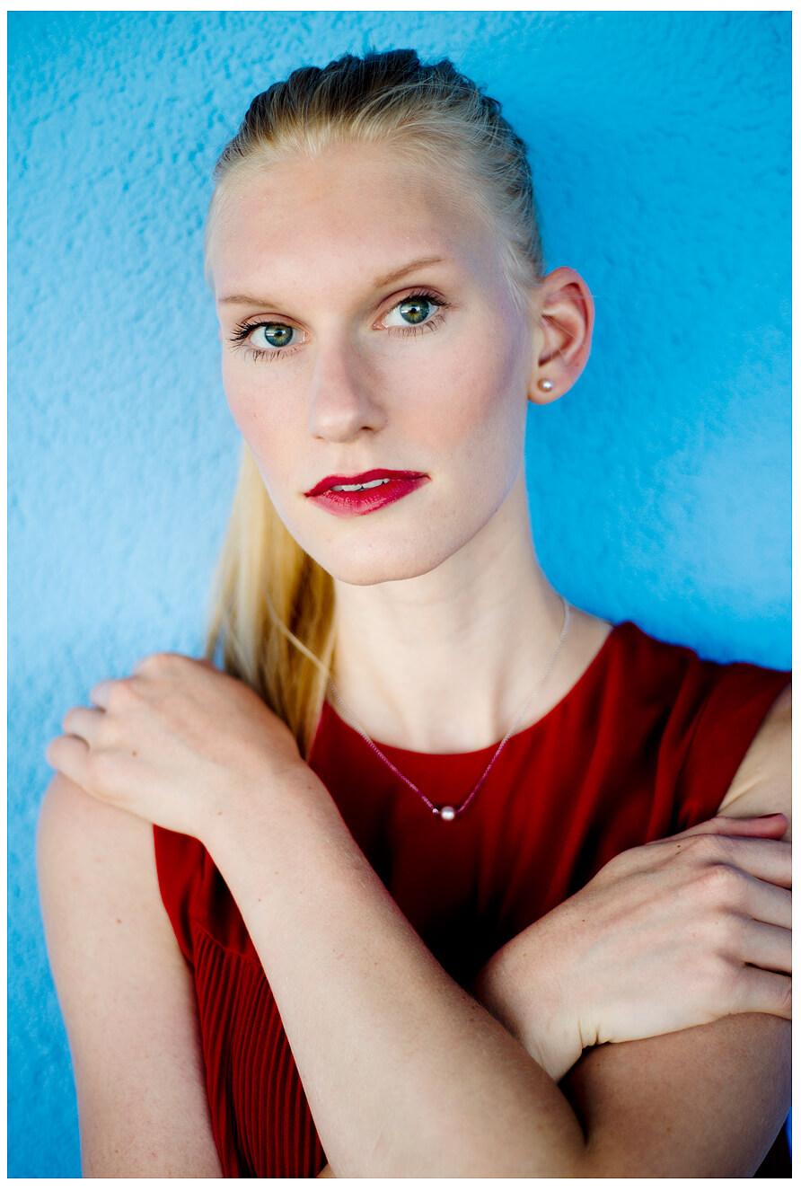 Fotograf in München fotografiert ein blondes Model an der blauen Wand, im Roten Oberteil, stehend