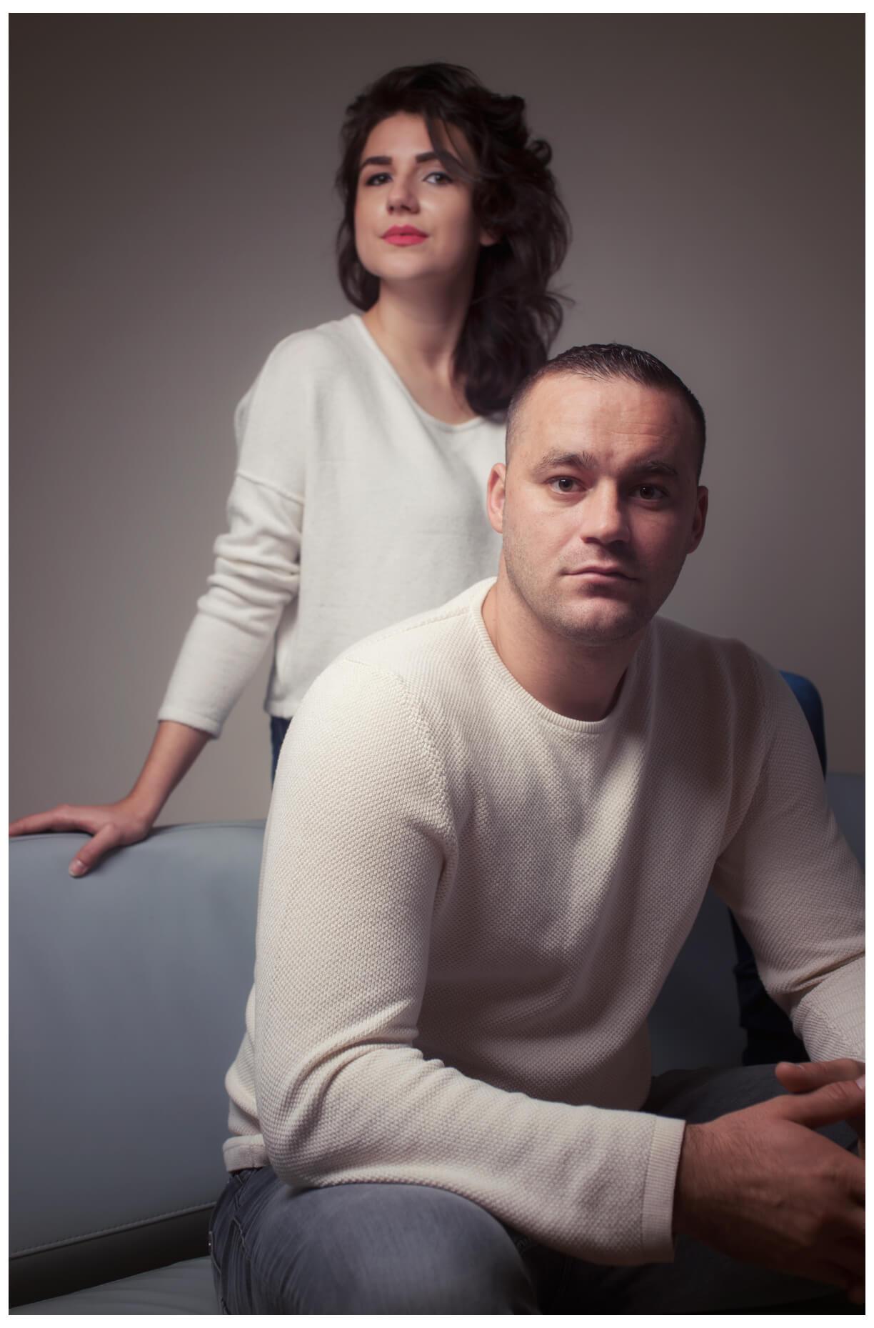 Paarshooting München, ein Paar im Fotostudio in weissen Pullis, sitzend, retro colors farbig