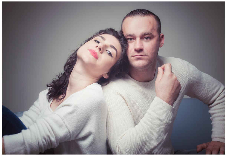 Paarshooting München, ein Paar im Fotostudio in weissen Pullis, sitzend, farbig