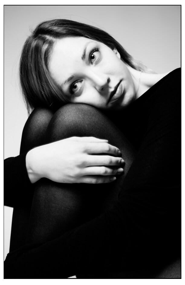 Portrait Schwarz-weiss einer sitzende Frau, umarmt Knie